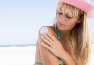 84460664 Woman On Beach Applying Sunblock