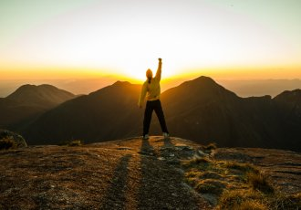 Thinkstockphotos 515369338 Man On Top Of A Mountain
