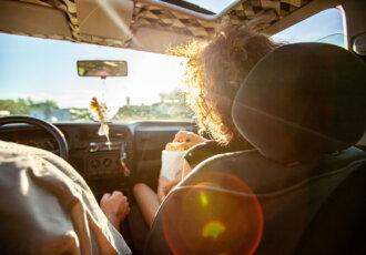 Woman snacking in car on roadtrip