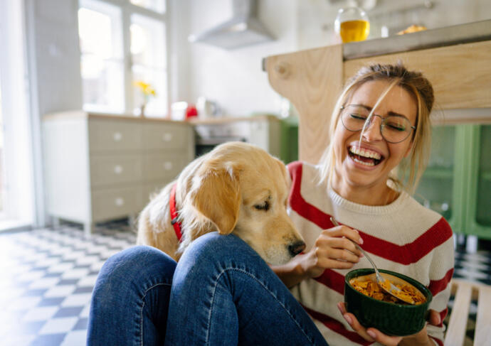 Girl eating cereal with dog