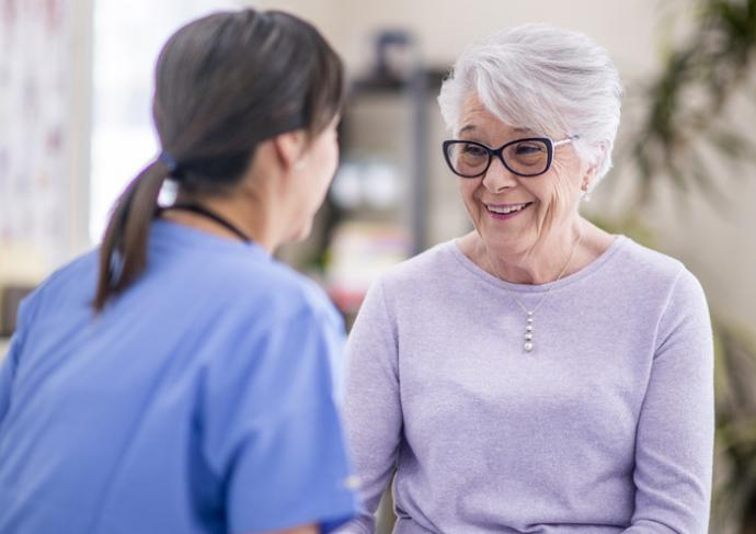 Happy Elderly Woman Talking with Healthcare Provider
