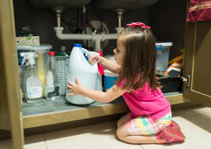 Little girl with bleach under sink