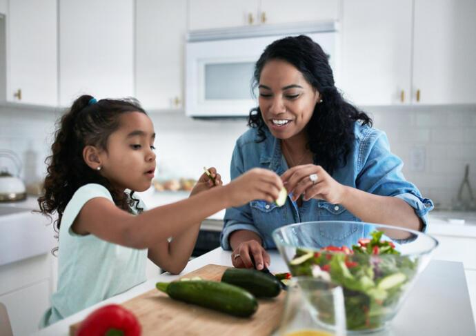 Mother daughter making food