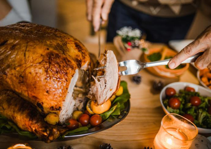 Person carving a turkey at the table