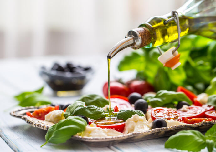 Pouring olive oil on salad