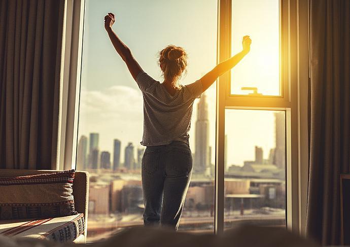 Thinkstockphotos 912257262 Woman Stretching Morning Window