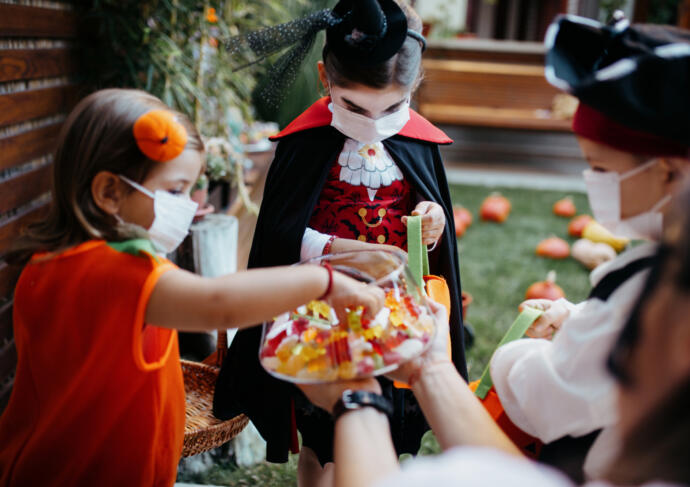 Trick or treaters in masks with healthy Halloween treat