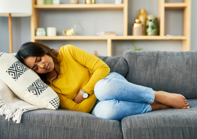 Woman laying on couch holding her stomach