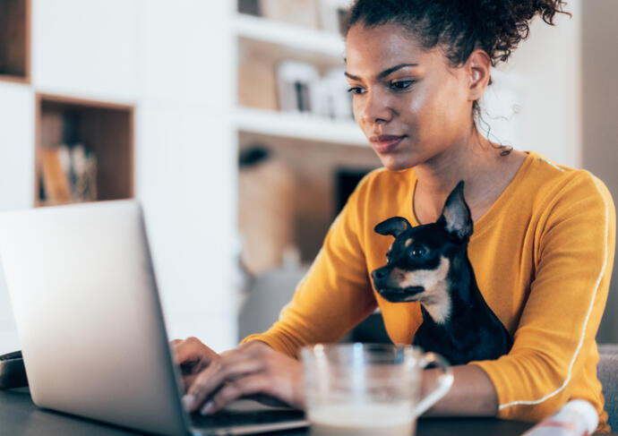 Woman looking at her computer with her dog