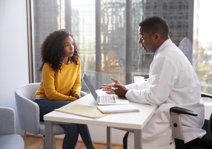 Woman talking with her doctor at his desk