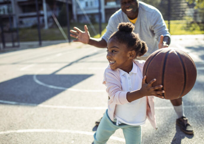 Little girl child playing basketball with father