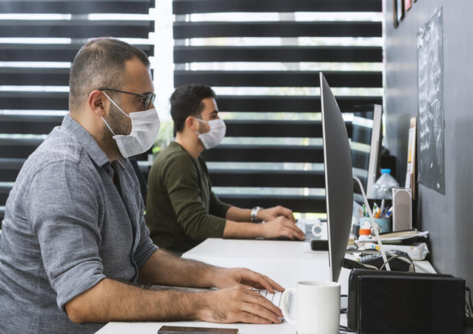 People working at computers with masks