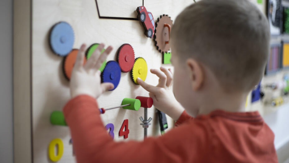 Boy playing with puzzle on wall