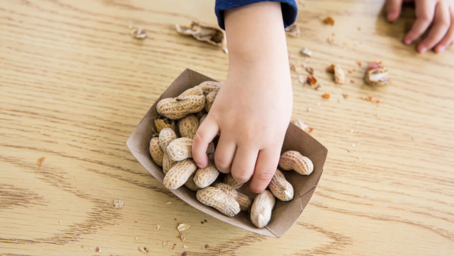 Child reaching for peanuts