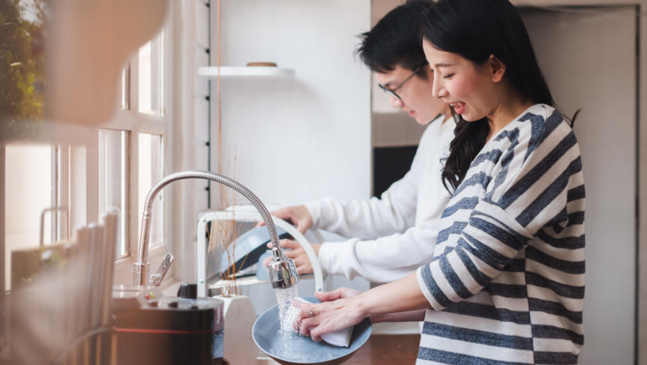 Couple cleaning dishes