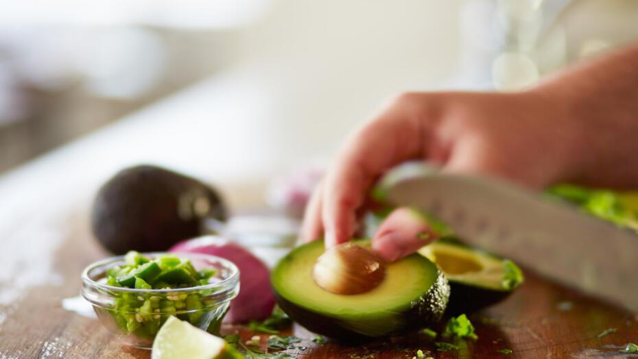 Man cutting avocado on cutting board