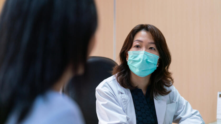 Doctor wearing mask talking to patient