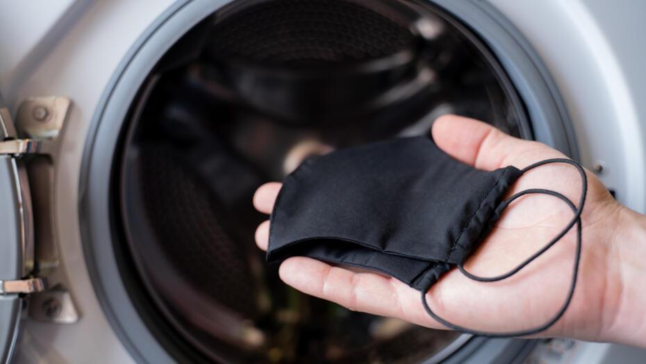 Person throwing mask into washing mashine