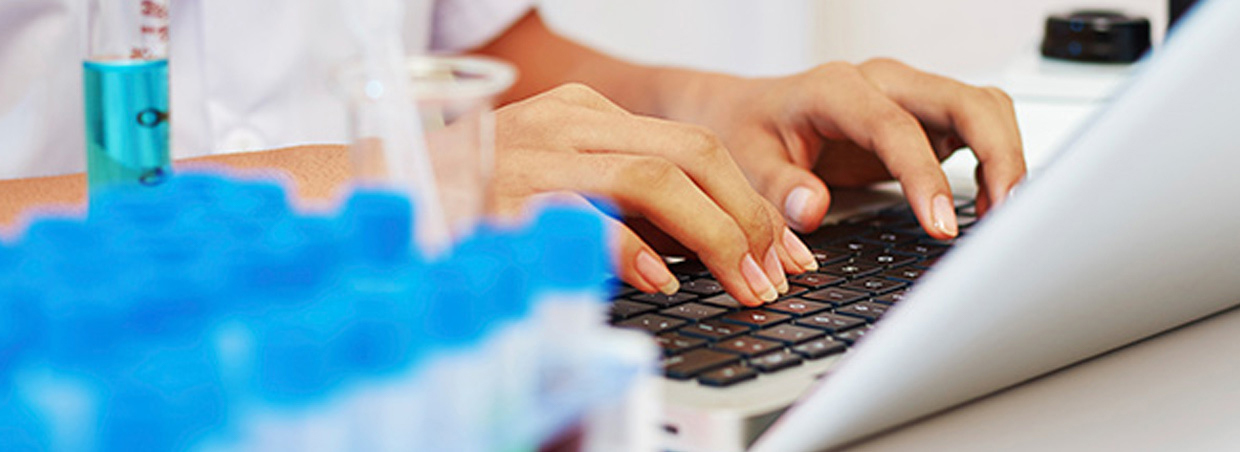 Lab Technician typing on a laptop next to test tubes